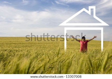young happy woman in the middle of the field enjoying new house - stock photo