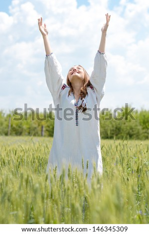 Young happy woman in traditional ukrainian dress standing in wheat field on summer day - stock photo