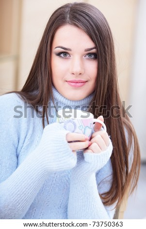 Young happy woman in warm sweater drinking a cup of hot tea - stock photo