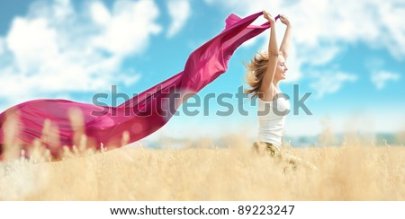 Young happy woman in wheat field with fabric. Summer picnic - stock photo