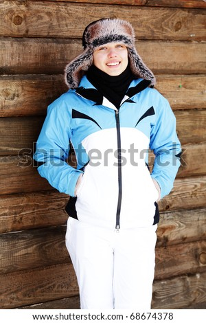 Young happy woman in winter cloths standing in front of wooden wall outdoors - stock photo