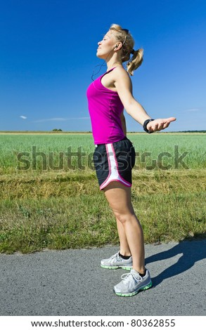 Young happy woman jogging relaxing after running, arms outstretched. Motivation and Inspiration Fitness Concept. Blue sky and green country landscape. Asphalt road on green village fields. - stock photo