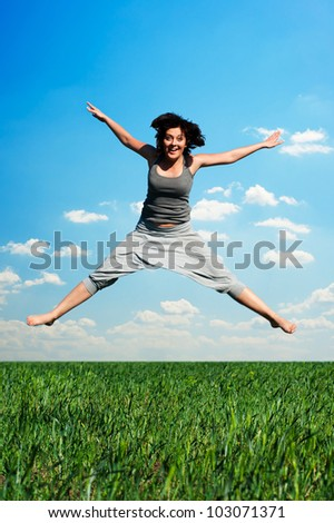 young happy woman jumping at the field - stock photo