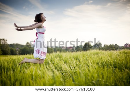 young happy woman jumping in the field - stock photo