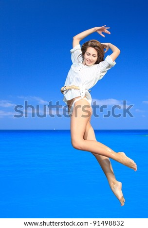 Young happy woman jumping on a beach - stock photo