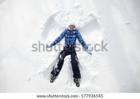 Young happy woman kidding on snow in winter day  - stock photo