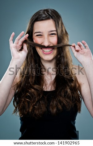 Young Happy Woman Laughing and Playing with Her Hair Over a Grey Background - stock photo