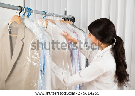 Young Happy Woman Looking At Clothes In Shop - stock photo