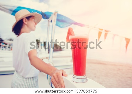 Young happy woman looking far away at sand beach with fresh watermelon juice (intentional sun glare, lens focus on glass) - stock photo