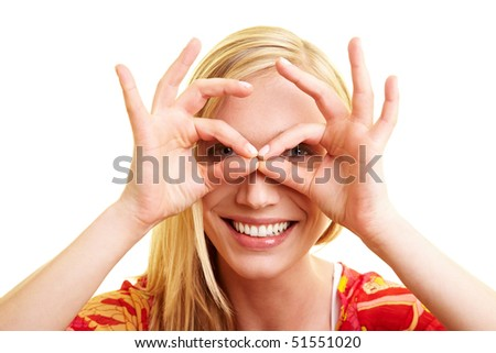 Young happy woman looking through a hole in her fingers - stock photo