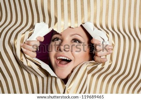 Young happy woman looking through paper hole - stock photo