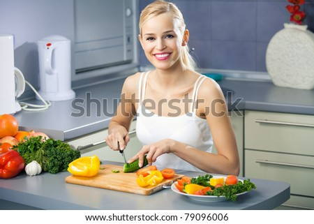 Young happy woman making salad at domestic kitchen
