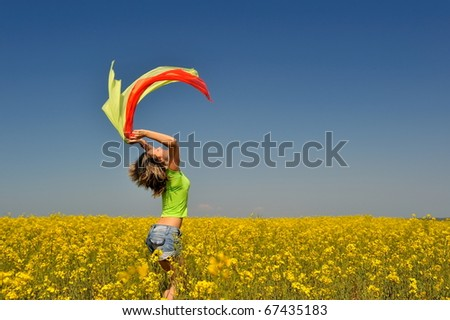 young happy woman on blooming rapeseed field in summer