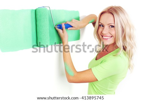 Young happy woman painting wall with paint roller - stock photo