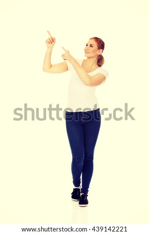Young happy woman pointing for copyspace or something - stock photo