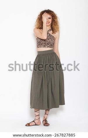 young happy woman posing in green skirt with animal print shirt, on white background - stock photo
