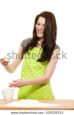 young happy woman preparing eggs for  baking with flour on white background - stock photo