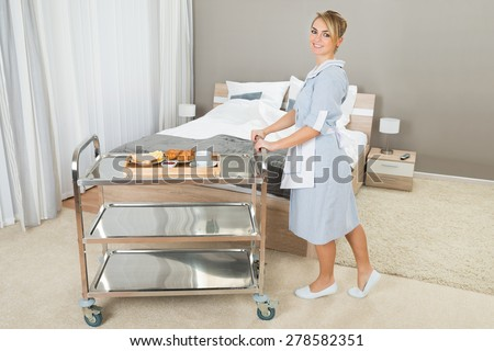 Young Happy Woman Pushing Trolley With Breakfast In Hotel Room - stock photo