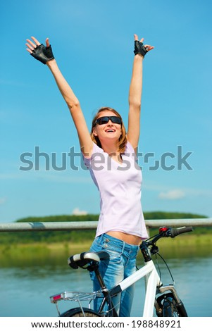 Young happy woman raised hands up in joy, outdoor shoot - stock photo