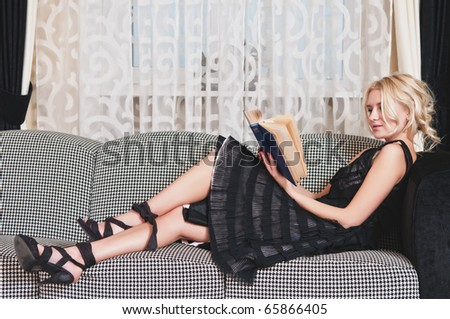 Young happy woman read book on sofa in living room - stock photo
