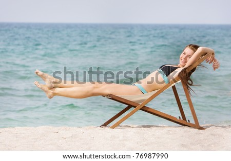 young happy woman relaxing on beach - stock photo