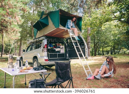 Young happy woman resting in a tent on the roof of vehicle while other woman putting hiking boots sitting on the grass - stock photo