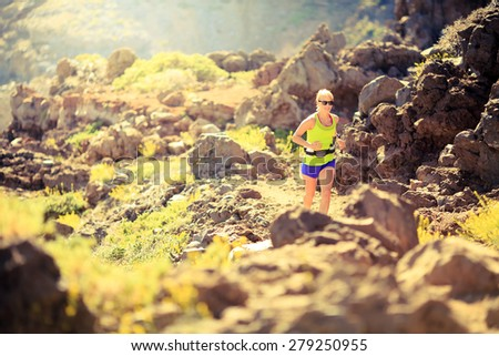 Young happy woman running in mountains on sunny summer sunset. Beauty female runner jogging and exercising outdoors in nature, rocky trail footpath volcanic wilderness landscape, freedom concept - stock photo