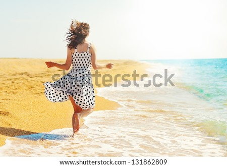 Young happy woman running on the beach back to camera - stock photo