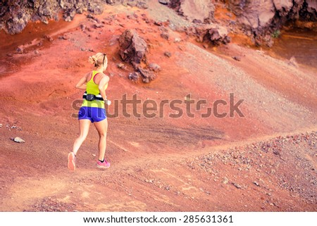 Young happy woman running or power walking in mountains on sunny summer day. Beautiful natural landscape and female runner jogging exercising outdoors in nature rocky trail on La Palma, Canary Islands - stock photo