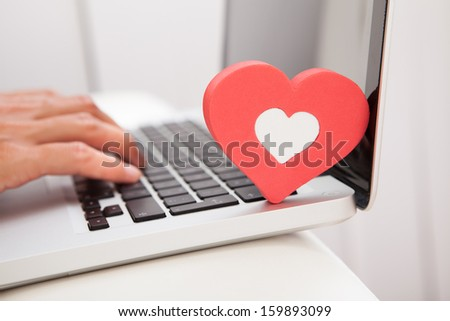 Young Happy Woman Showing Heart Shape While Using Laptop On Couch - stock photo