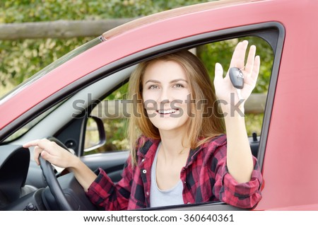 Young happy woman shows car key out of window