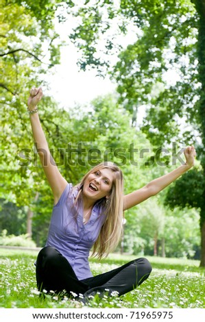 Young happy woman siting in grass with flowers enjoying life
