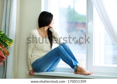Young happy woman sitting on a window-sill and looking outside - stock photo