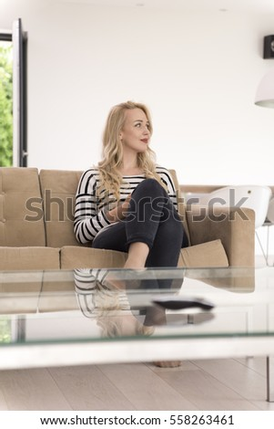 young happy woman sitting on sofa with mobile phone at luxury home