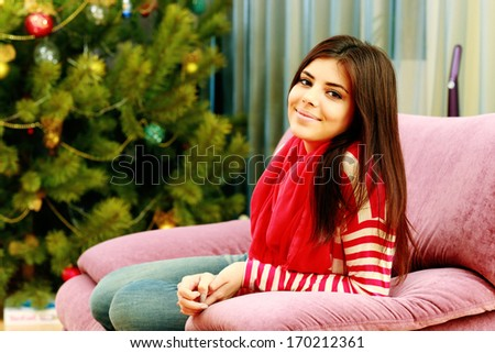 Young happy woman sitting on the sofa at home - stock photo
