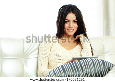 Young happy woman sitting on the sofa with tablet computer and looking at camera - stock photo