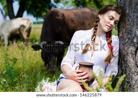 Young happy woman sitting tired near cows in countryside on summer day - stock photo