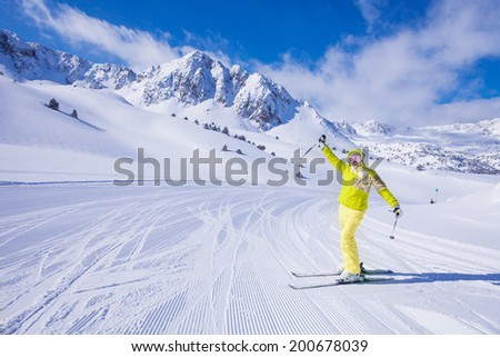 Young happy woman skier stand with lifted from excitement hands on the piste - stock photo