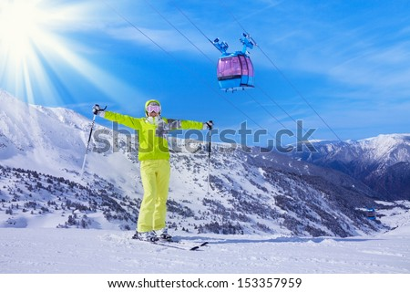 Young happy woman skier stand with lifted from excitement hands with cable car sky lift and mountains on background - stock photo