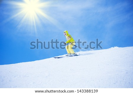 Young happy woman sliding downhill with clean white snow and blue sky with sun on background - stock photo