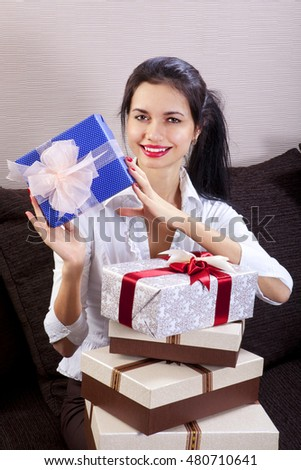 Young happy woman smiling and holds gift box in hands
