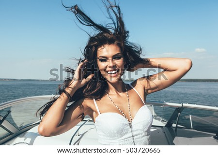 Young happy woman smiling on the luxury boat in open sea in summer. Caucasian female model having fun