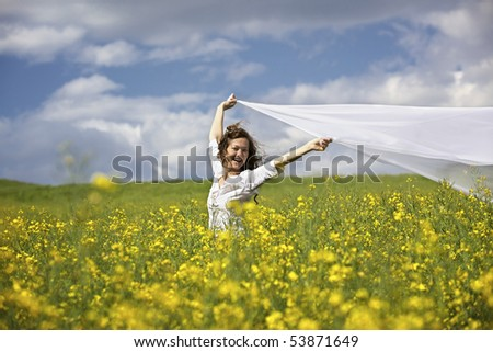 Young happy woman standing in yellow rapeseed field holding a white long piece of cloth in the wind.