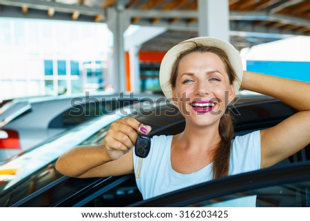 Young happy woman standing near a car with keys in hand - concept of buying a used car - stock photo