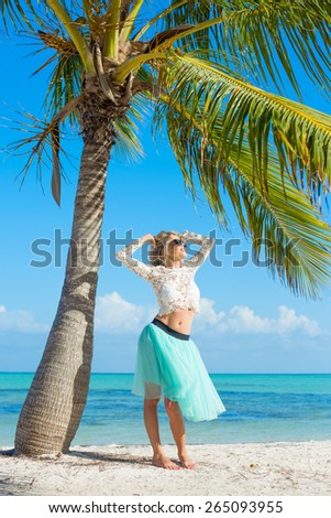 Young happy woman standing on beach under palm tree - stock photo