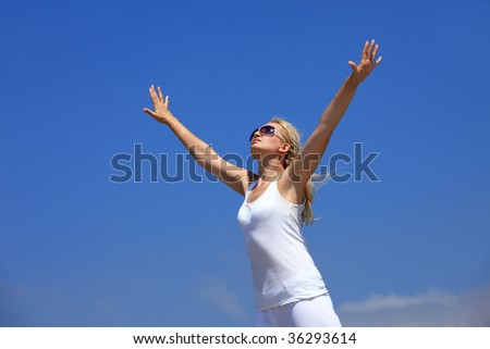 Young happy woman stretching hands on a blue sky background - stock photo