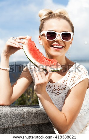 Young happy woman takes watermelon from the opened fridge full of vegetables and fruit. Concept of healthy and dieting food