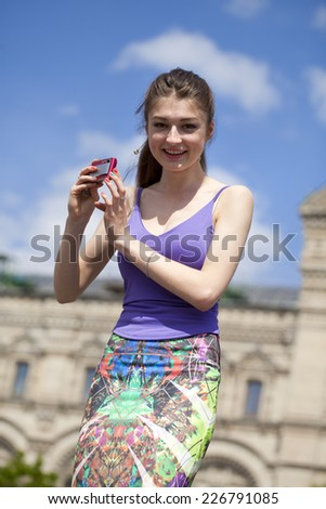 Young happy woman taking pictures on your camera on Red Square, Moscow