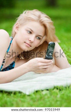 Young happy woman texting on mobile phone. SMS - stock photo