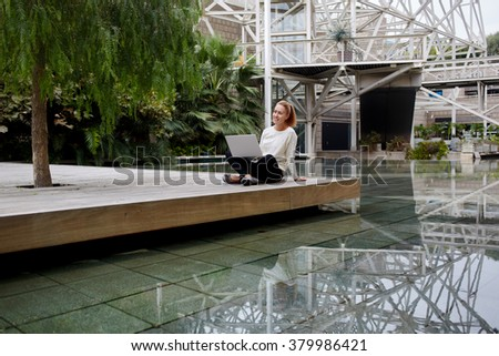 Young happy woman thinking about something after watching a good movie on a laptop computer, hipster girl with cute smile enjoying rest after work on portable net-book while sitting in hotel outside - stock photo